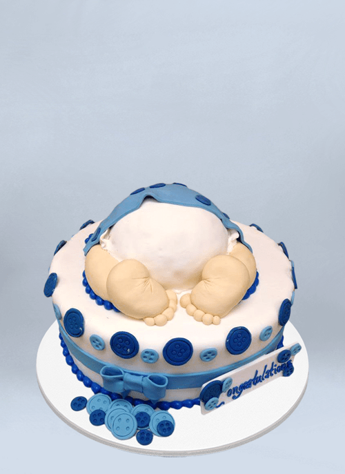 Photo: 1 tier cake with blue bows and buttons and baby butt and feet sticking out of top.