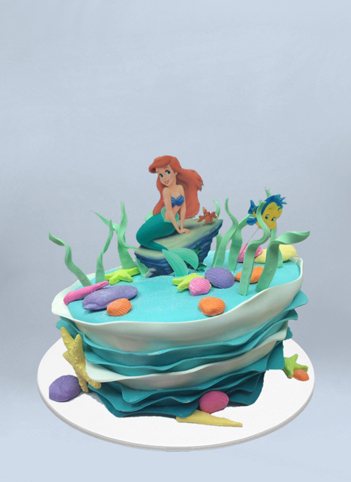 Photo: fondant topsy cake with waves and little mermaid Ariel sitting on top