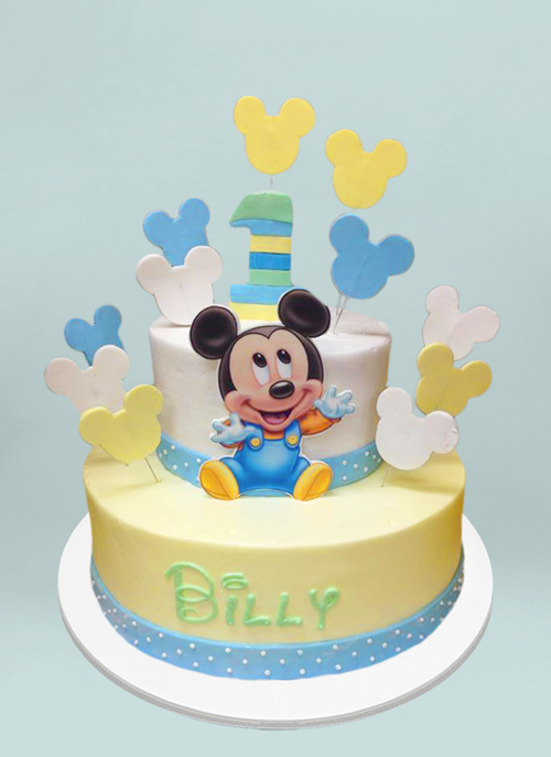 Photo: baby mickey on 2 tier cake with disney writing