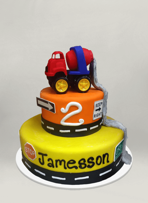 Photo: fondant cake with 3d construction truck dripping cement down the two tiers, road signs around the tiers